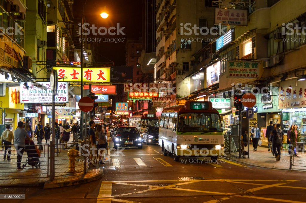 This is a busy street in Hong Kong with colorful signs, many...