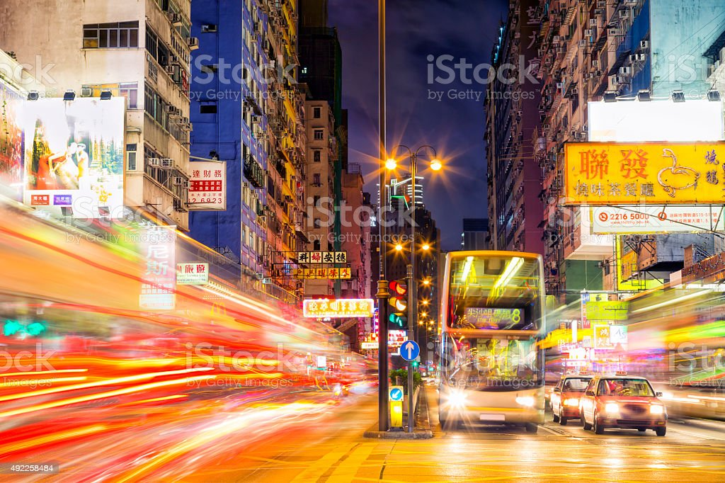 Illuminated busy street with car light trails, advertising signs...