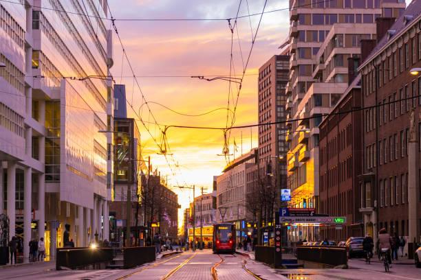 Belebte Straße mit Straßenbahn- und Bürogebäuden bei Sonnenuntergang in Den Haag, Niederlande – Foto