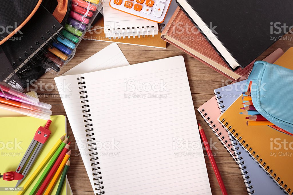 Busy student's desk with blank folded notebook royalty-free stock photo