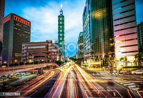 Motion blur on busy streets during rush hour at dusk in Taipei's city centre.