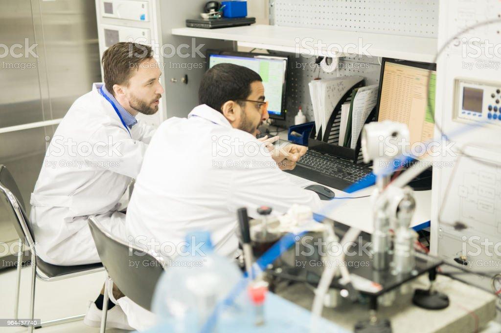 Técnicos ocupados, exibindo dados no escritório da fábrica - Foto de stock de Adulto royalty-free