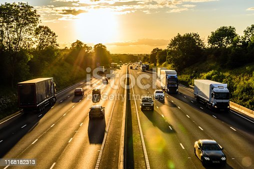 busy traffic on uk motorway road overhead view at sunset.