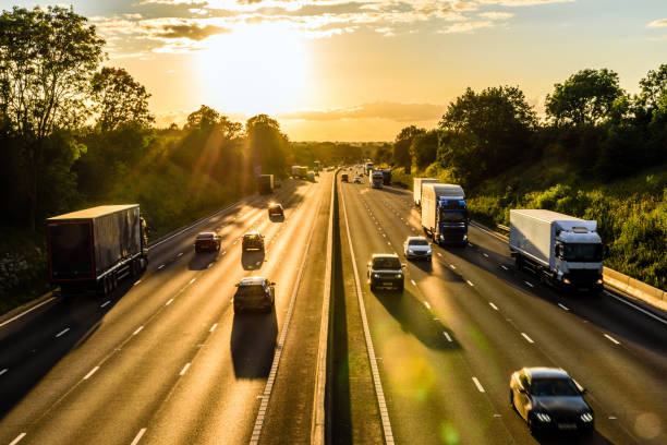 busy traffic on uk motorway road overhead view at sunset busy traffic on uk motorway road overhead view at sunset. multiple lane highway stock pictures, royalty-free photos & images