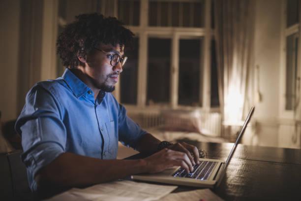 estudante de universidade ocupado estudando à noite - college people laptop - fotografias e filmes do acervo