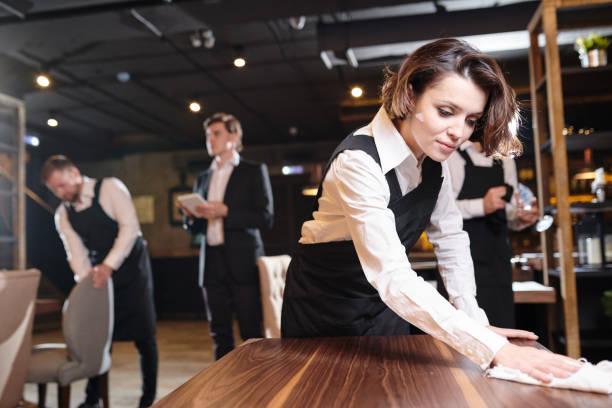Beschäftigt Kellnerin offenen Restaurant vorbereiten und die Bereinigung – Foto