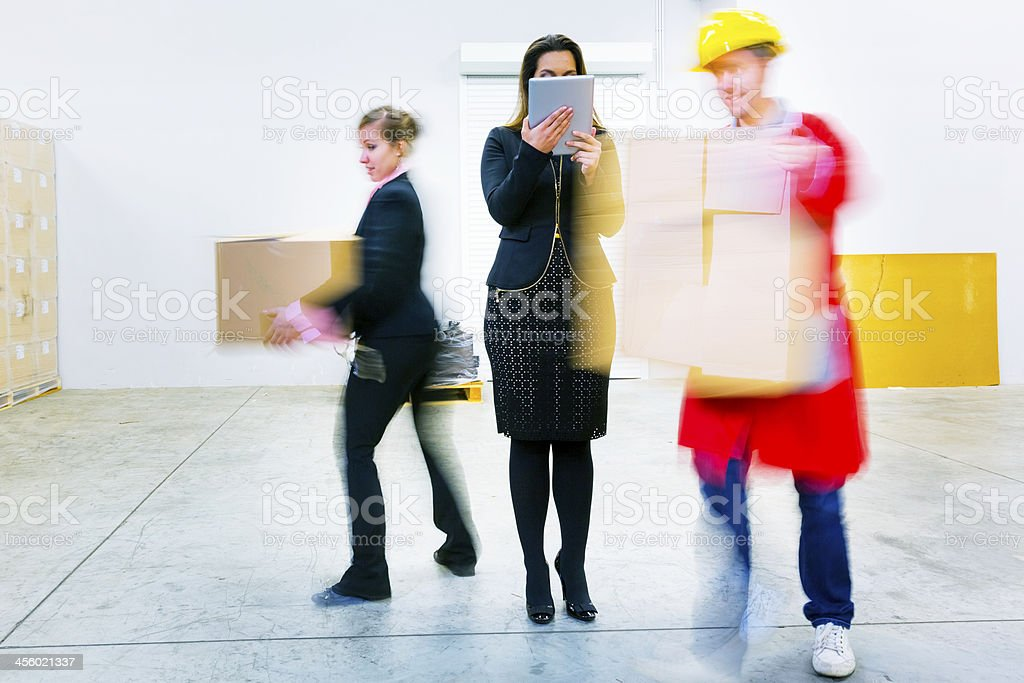 Busy warehouse action with supervisor using digital tablet stock photo