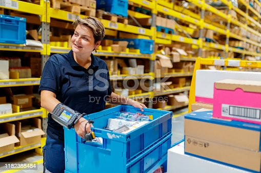 Busyt female warehouse worker, holding full crate in warehouse