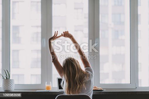 Waist up photo of young lady during a break sitting by the table and stretching her arms from hard work