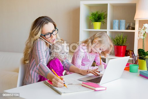 Busy woman trying to work with laptop while babysitting two kids