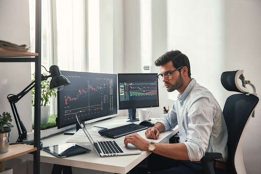 istock Busy working day. Young bearded trader in eyeglasses working with laptop while sitting in his modern office in front of computer screens with trading charts. 1147352265