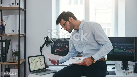 Busy working day. Young successful trader or businessman in formal wear and eyeglasses sitting at modern office against computer screens with charts and reading market report. Stock broker. Forex market. Trade concept