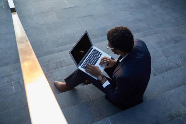 Beschäftigt junge schwarze Mann mit Afro-Frisur sitzt auf Außentreppe und mit Laptop bei der Untersuchung von Online-Dateien – Foto