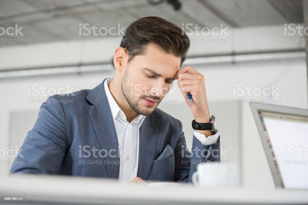 Busy young businessman at work Portrait of young businessman looking busy working at is office. 25-29 Years Stock Photo