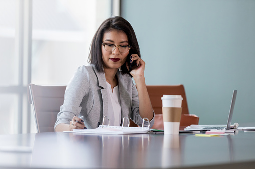 Busy young woman talks on smart phone at work