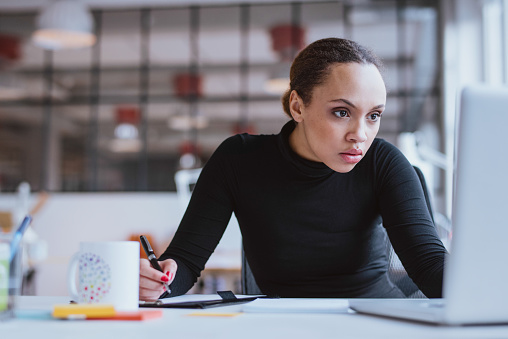 Busy Young Woman Working At Her Desk Stock Photo - Download Image Now