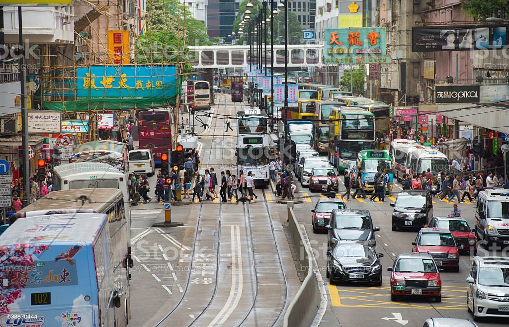 Busy zebra crossing in Hong Kong Evening, crowded and rainy. Typical trams, taxis and buses. Adult Stock Photo
