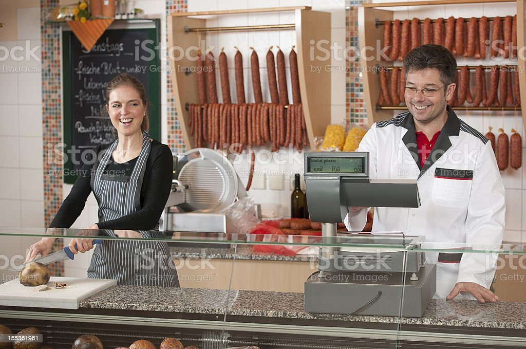 Butcher and female sales executive behind counter royalty-free stock photo