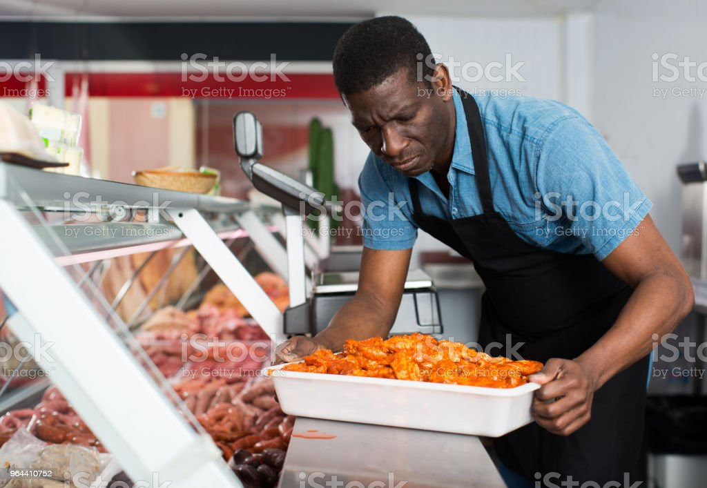 Butcher arranging meat display - Royalty-free Adult Stock Photo