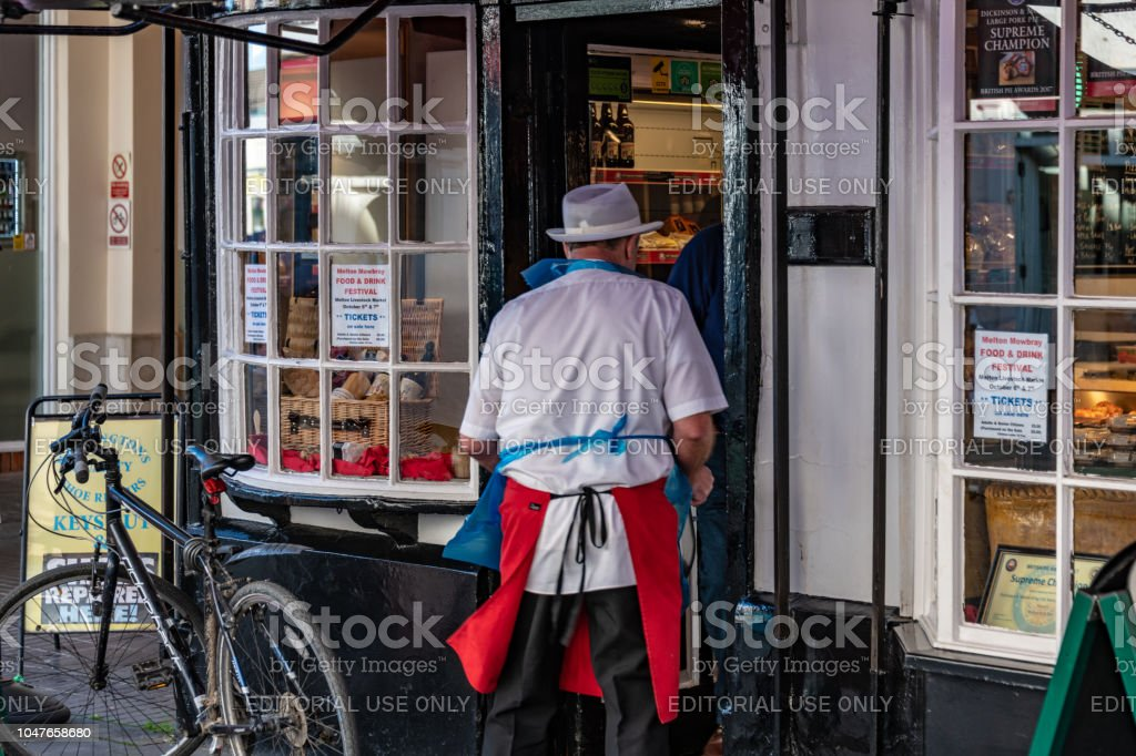 07d90ebc62fc8 Butcher carries meat into Ye Olde Pork Pie Shoppe in Melton Mowbray  royalty-free stock