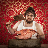 Butcher cutting beef meat on a wooden table on the dark background