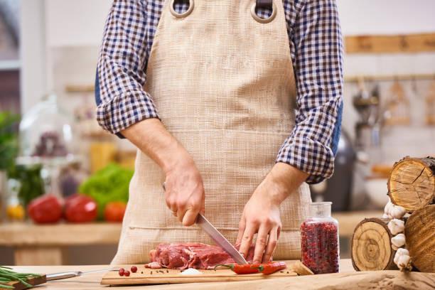 metzger schneiden fleisch von schwein, rind oder hammel steak auf küche mit gemüse-hintergrund - grillschürze stock-fotos und bilder