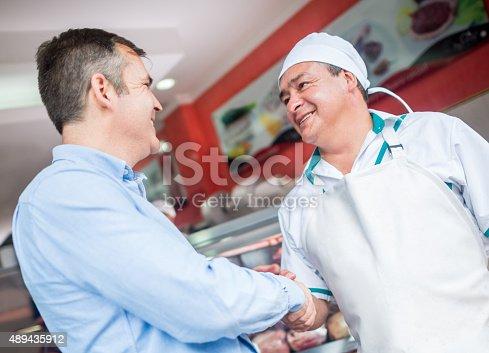 istock Butcher handshaking with a happy customer 489435912