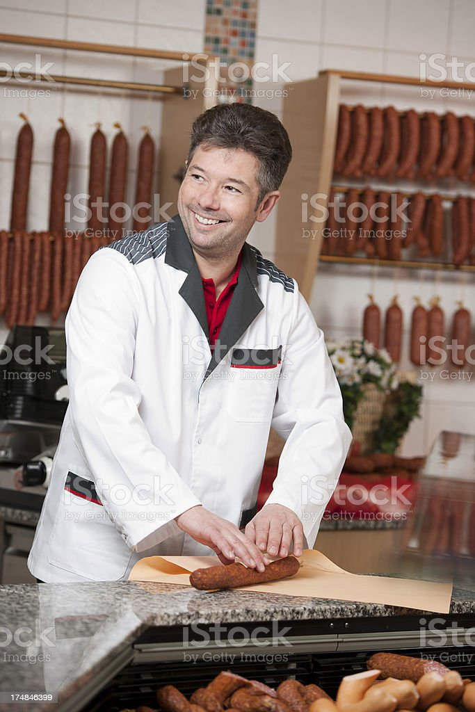 Butcher is packing sausage royalty-free stock photo