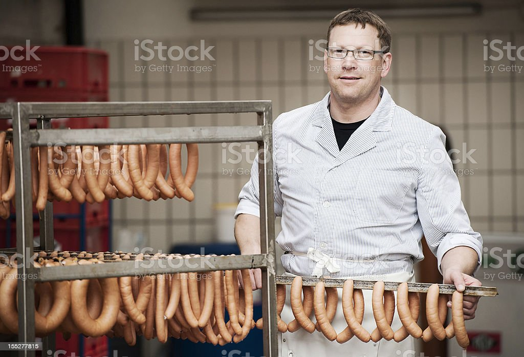 Butcher with fresh sausages stock photo