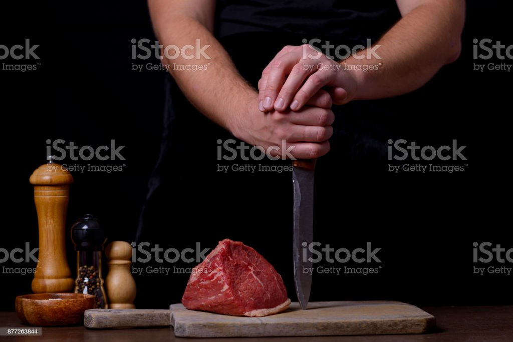 Butcher with knife and raw steak and spices on table stock photo