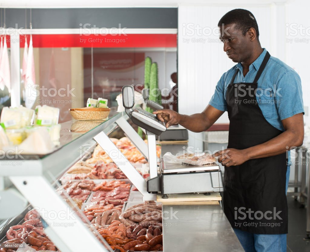 Butcher working behind counter - Royalty-free Adult Stock Photo