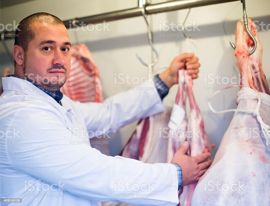 butcher working with meat in store stock photo
