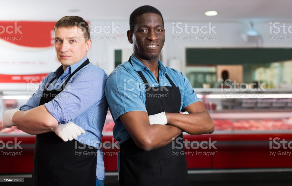 butchers standing in hall of butcher shop - Royalty-free Activity Stock Photo