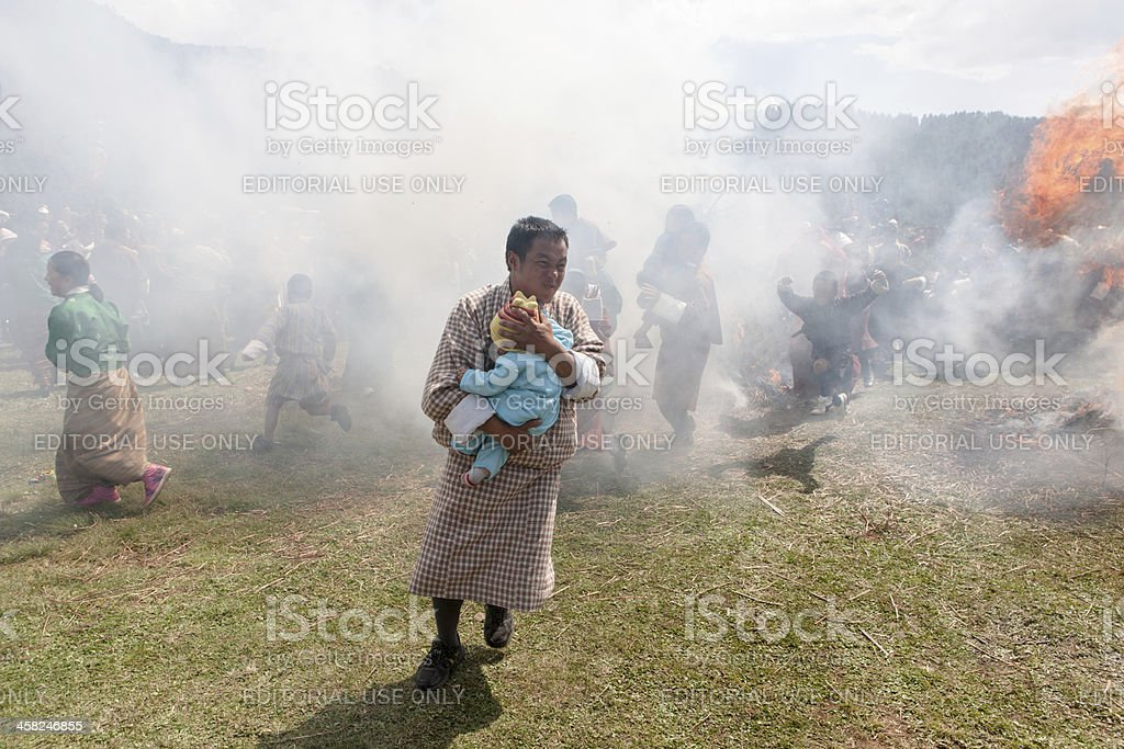 Buthanese man holding baby jumps through two burning haystacks royalty-free stock photo
