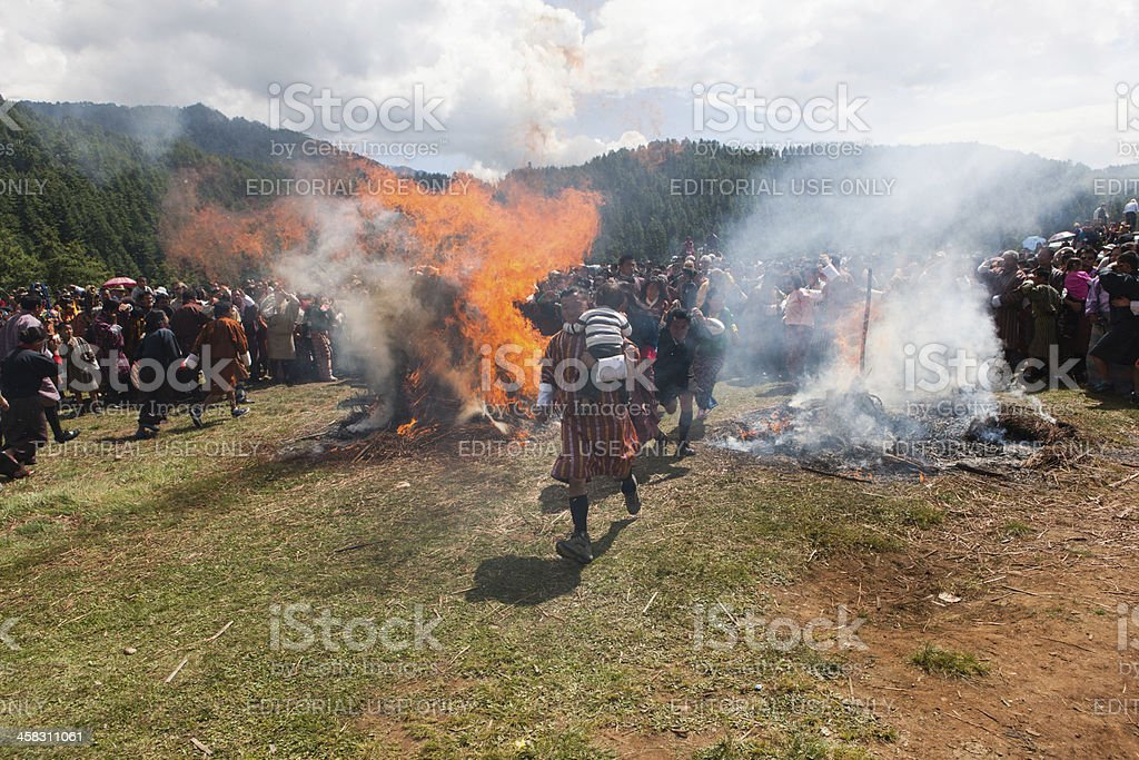 Buthanese man holding baby jumps through two burning haystacks foto