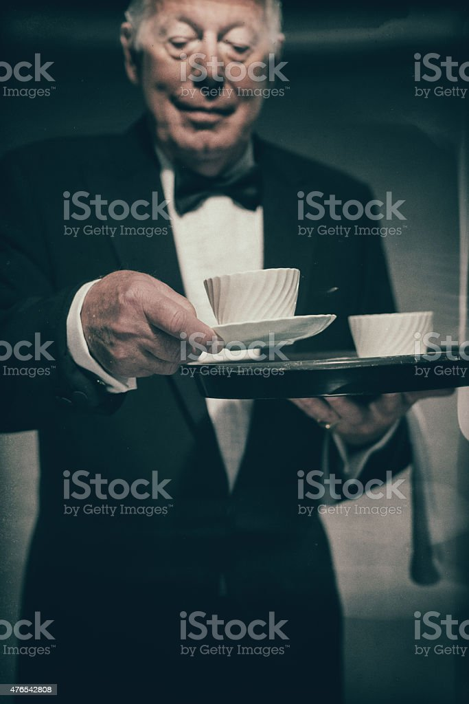 Butler Carrying Tray of Mugs and Serving Coffee stock photo