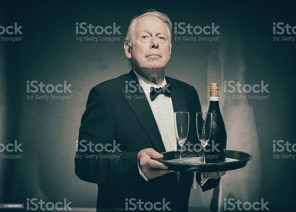 Butler Carrying Tray with Champagne and Glasses stock photo