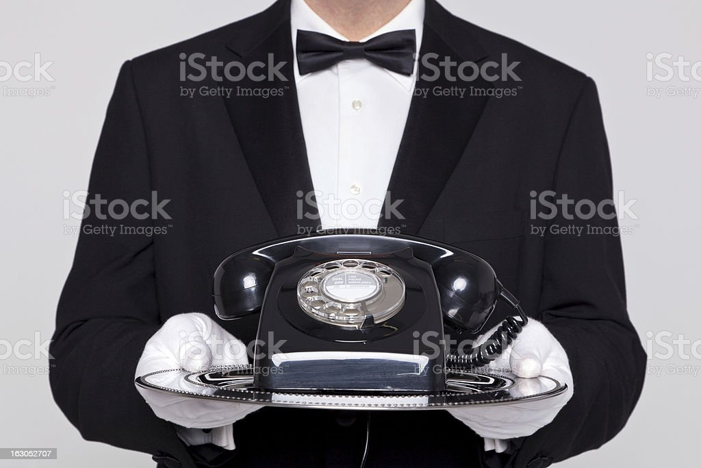 Butler holding a telephone on silver tray royalty-free stock photo
