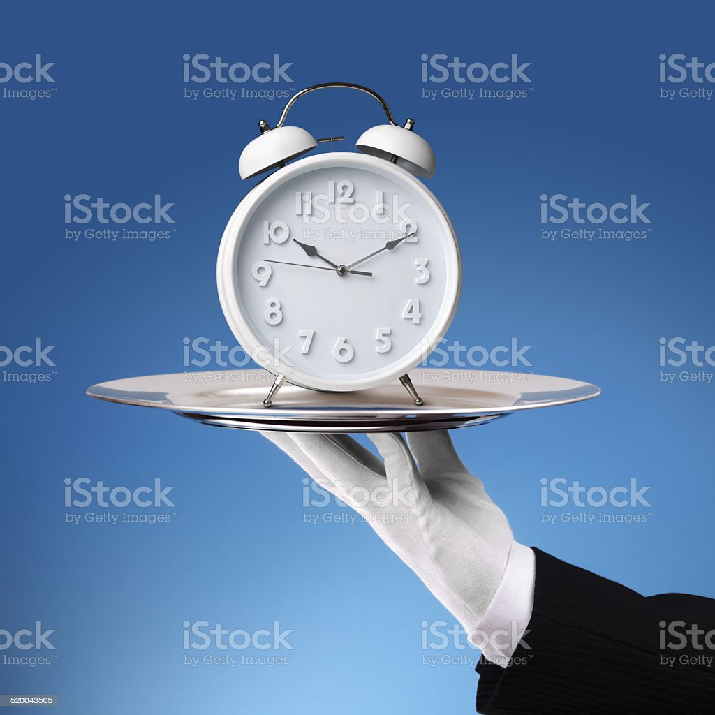 Butler holding silver tray with a alarm clock stock photo