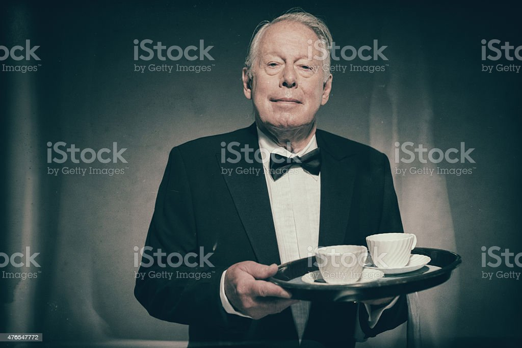 Butler Holding Tray of White Coffee Cups stock photo