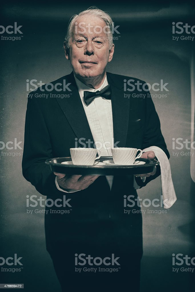 Butler Holding Tray of White Tea Cups stock photo
