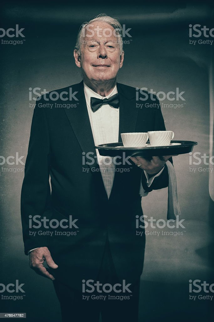 Butler Holding White Coffee Cups on Tray stock photo