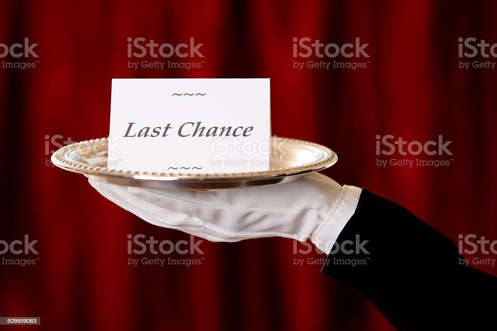 Butler holds 'Last Chance' notecard on silver platter. Red curtains. stock photo