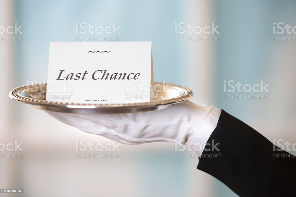 Butler holds 'Last Chance' notecard on silver platter. Window. stock photo