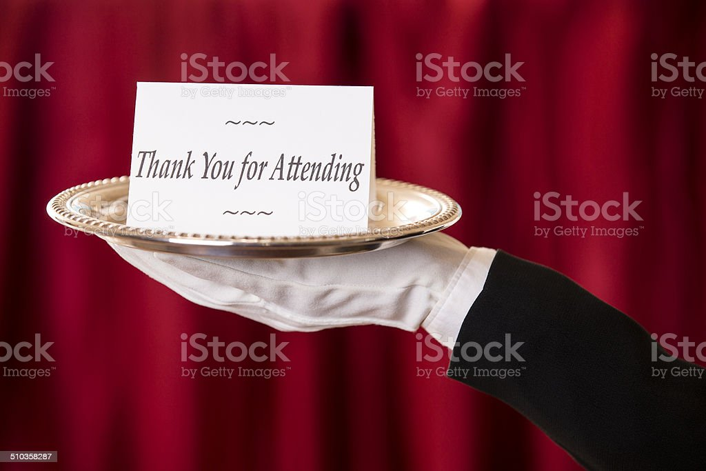 Butler holds 'Thank you for Attending' notecard on silver platter. stock photo
