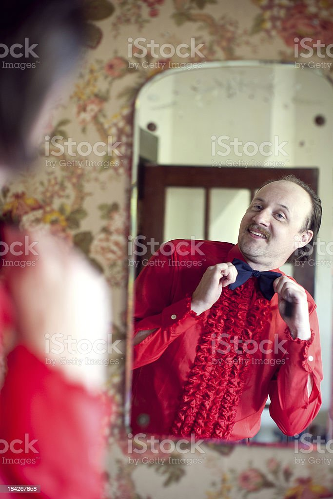 Butler In Red Shirt & Bow Tie Looking At Mirror royalty-free stock photo