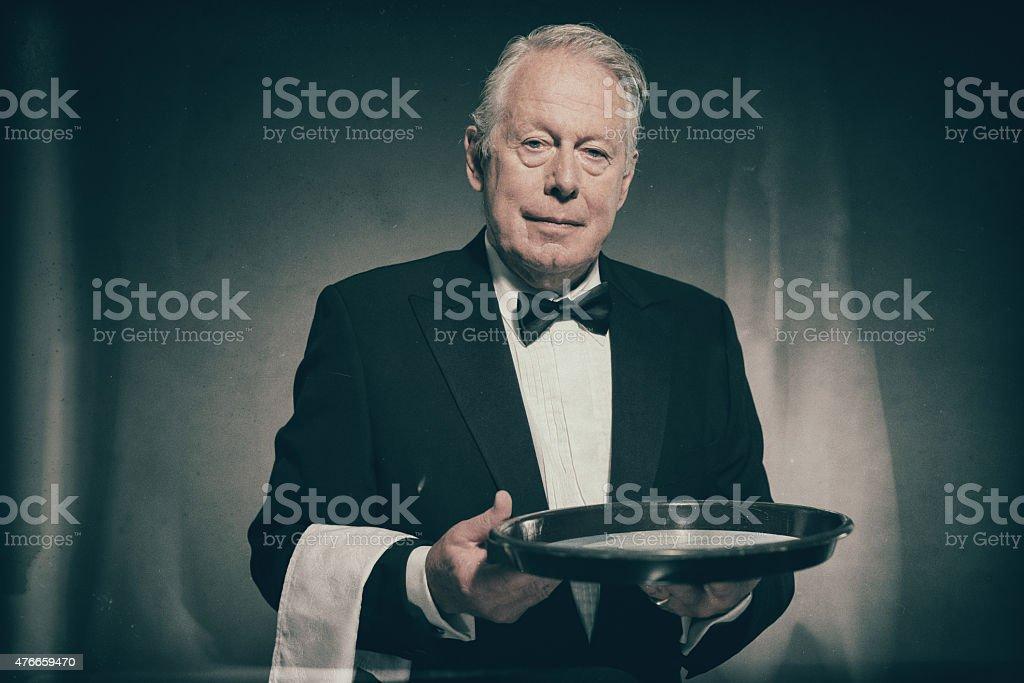 Butler Wearing Tuxedo Carrying Empty Tray stock photo
