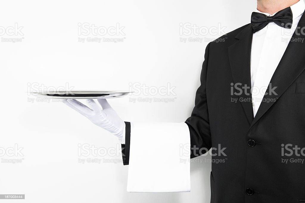 Butler wearing white glove and napkin holding silver tray stock photo