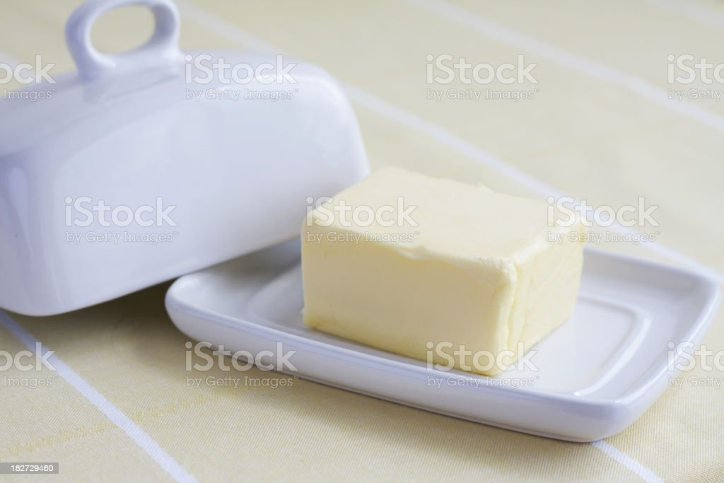 Butter block on white ceramic butter container on yellow background royalty-free stock photo