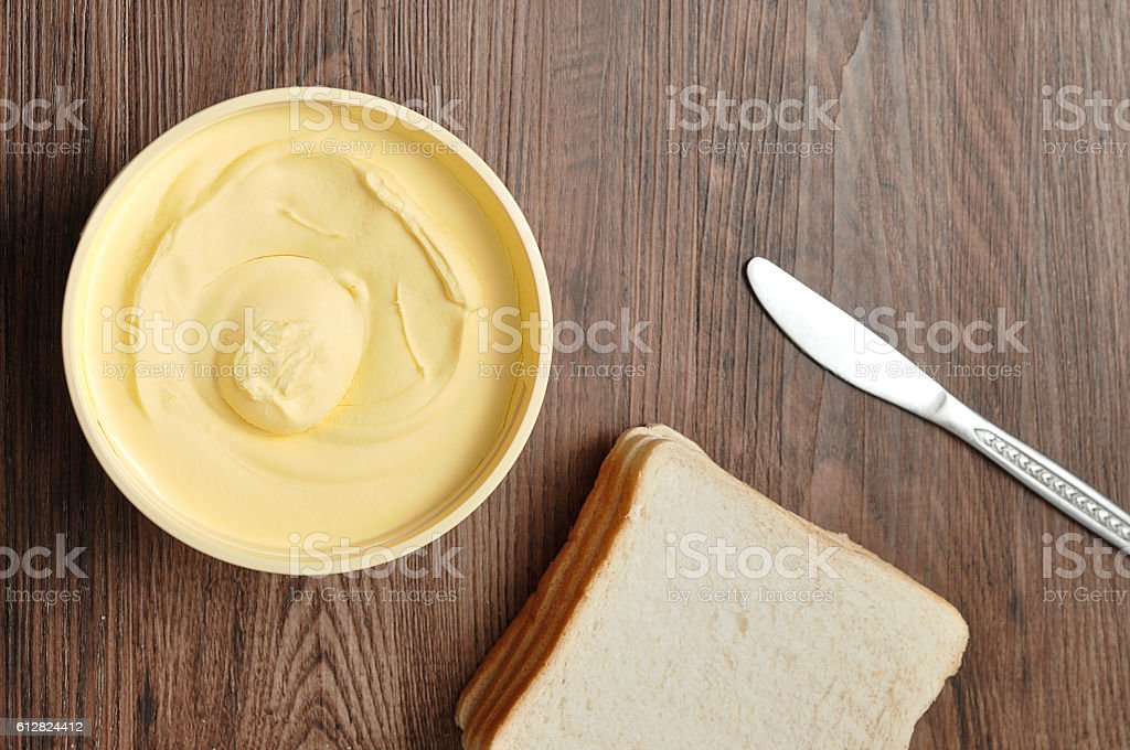 Butter, bread and a knife isolated on a wooden background stock photo